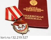 Купить «Орден Красного Знамени (орден «Красное знамя») лежит на орденской книжке. Крупный план», эксклюзивное фото № 32219527, снято 15 апреля 2019 г. (c) Игорь Низов / Фотобанк Лори