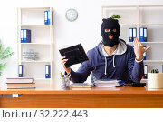 Male thief in balaclava in the office. Стоковое фото, фотограф Elnur / Фотобанк Лори