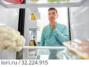 man looking for food in fridge at kitchen. Стоковое фото, фотограф Syda Productions / Фотобанк Лори