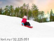 Купить «happy little girl sliding down on sled in winter», фото № 32225051, снято 10 февраля 2018 г. (c) Syda Productions / Фотобанк Лори