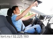 Купить «man or car driver adjusting mirror», фото № 32225183, снято 25 августа 2019 г. (c) Syda Productions / Фотобанк Лори