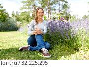 Купить «young woman and lavender flowers at summer garden», фото № 32225295, снято 12 июля 2019 г. (c) Syda Productions / Фотобанк Лори