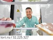 Купить «man taking food from fridge at kitchen», фото № 32225327, снято 5 июля 2019 г. (c) Syda Productions / Фотобанк Лори