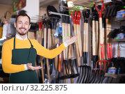 Купить «Smiling male seller demonstrating assortment», фото № 32225875, снято 2 марта 2017 г. (c) Яков Филимонов / Фотобанк Лори