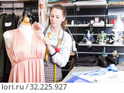 Купить «Female seamstress is thinking about new dress for collection of clothes near mannequin», фото № 32225927, снято 5 мая 2018 г. (c) Яков Филимонов / Фотобанк Лори