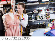 Female seamstress is thinking about new dress for collection of clothes near mannequin. Стоковое фото, фотограф Яков Филимонов / Фотобанк Лори