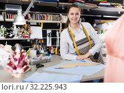 Woman professional measuring material at sewing workshop. Стоковое фото, фотограф Яков Филимонов / Фотобанк Лори