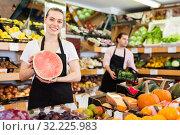 Купить «Young woman seller holding half of watermelon in hands in fruit store», фото № 32225983, снято 27 апреля 2019 г. (c) Яков Филимонов / Фотобанк Лори