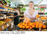 Купить «Woman customer holding bag with fresh oranges on supermarket», фото № 32225991, снято 27 апреля 2019 г. (c) Яков Филимонов / Фотобанк Лори