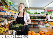 Купить «Young female seller standing with box of green beans in shop», фото № 32226003, снято 27 апреля 2019 г. (c) Яков Филимонов / Фотобанк Лори