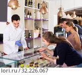 Купить «Couple with woman friend are choosing cakes from showcase», фото № 32226067, снято 5 июня 2017 г. (c) Яков Филимонов / Фотобанк Лори