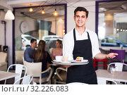 Купить «Adult waiter is warmly welcoming guests», фото № 32226083, снято 5 июня 2017 г. (c) Яков Филимонов / Фотобанк Лори