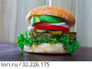 Купить «Vegetarian hamburger with soybean patty, fresh vegetables and avocado at plate», фото № 32226175, снято 11 июля 2020 г. (c) Яков Филимонов / Фотобанк Лори