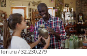 Купить «Afro-american seller offers woman traditional handmade african pottery», видеоролик № 32230279, снято 28 мая 2020 г. (c) Яков Филимонов / Фотобанк Лори