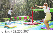 Купить «Funny adult friends are jumping on an inflatable trampoline», видеоролик № 32230307, снято 8 июля 2020 г. (c) Яков Филимонов / Фотобанк Лори