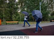 Люди идут с зонтиками в парке города Москвы в дождливую погоду и с сильным ветром, Россия (2019 год). Редакционное фото, фотограф Николай Винокуров / Фотобанк Лори