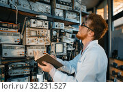 Купить «Strange engineer with book, test in laboratory», фото № 32231527, снято 17 июня 2019 г. (c) Tryapitsyn Sergiy / Фотобанк Лори