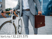 Businessman with briefcase and bicycle in downtown. Стоковое фото, фотограф Tryapitsyn Sergiy / Фотобанк Лори