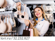 Female customer deciding on pretty bra. Стоковое фото, фотограф Яков Филимонов / Фотобанк Лори