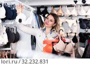 Купить «Smiling woman shopper choosing bras in shop», фото № 32232831, снято 20 марта 2017 г. (c) Яков Филимонов / Фотобанк Лори