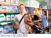Portrait of happy boy with dog during selecting dry food in petshop, woman on background. Стоковое фото, фотограф Яков Филимонов / Фотобанк Лори