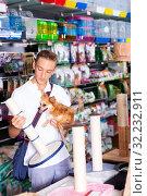 Купить «teenager with dog in hands looking for cat scratching post», фото № 32232911, снято 30 марта 2020 г. (c) Яков Филимонов / Фотобанк Лори