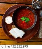Купить «Ukrainian borscht red-beet soup on bowl, served with bread and salo», фото № 32232975, снято 3 апреля 2020 г. (c) Яков Филимонов / Фотобанк Лори