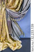 Комбинированные двусторонние шторы из золотой ткани с орнаментом и серым материалом и шнур с роскошной кисточкой. Стоковое фото, фотограф Светлана Васильева / Фотобанк Лори