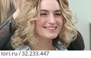 Купить «The final styling of curly hair of model by hairdresser in beauty salon», видеоролик № 32233447, снято 14 апреля 2017 г. (c) Vasily Alexandrovich Gronskiy / Фотобанк Лори