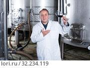 Купить «Adult wine maker controls quality of wine», фото № 32234119, снято 12 октября 2016 г. (c) Яков Филимонов / Фотобанк Лори