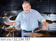 Musician male is choosing drum set and playing on it in music shop. Стоковое фото, фотограф Яков Филимонов / Фотобанк Лори