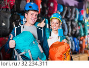 positive couple of travelers at sports store, selects backpacks for camping. Стоковое фото, фотограф Яков Филимонов / Фотобанк Лори