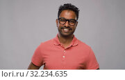 Купить «young indian man in glasses over grey background», видеоролик № 32234635, снято 12 сентября 2019 г. (c) Syda Productions / Фотобанк Лори