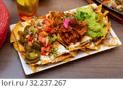 Купить «Corn chips nachos with homemade guacamole sauce, meat, cheese», фото № 32237267, снято 3 апреля 2020 г. (c) Яков Филимонов / Фотобанк Лори