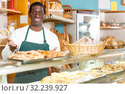 Glad African American man offering pastry. Стоковое фото, фотограф Яков Филимонов / Фотобанк Лори