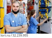 Купить «Portrait of male and female professional paramedicals near ambulance car», фото № 32239955, снято 30 ноября 2018 г. (c) Яков Филимонов / Фотобанк Лори