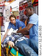 Купить «active ambulance team providing medical care to male patient in ambulance car», фото № 32240003, снято 30 ноября 2018 г. (c) Яков Филимонов / Фотобанк Лори