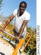 Купить «Active african american man doing workout at pull-up bar in park», фото № 32240043, снято 3 ноября 2018 г. (c) Яков Филимонов / Фотобанк Лори