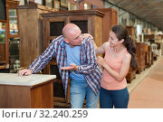 Купить «Cheerful couple looking for vintage drawer chest», фото № 32240259, снято 22 мая 2019 г. (c) Яков Филимонов / Фотобанк Лори