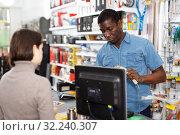 Купить «Household store seller working with client», фото № 32240307, снято 21 января 2019 г. (c) Яков Филимонов / Фотобанк Лори