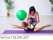 Купить «Girl and mother exercising at home», фото № 32241227, снято 16 июля 2019 г. (c) Elnur / Фотобанк Лори