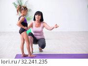Купить «Girl and mother exercising at home», фото № 32241235, снято 16 июля 2019 г. (c) Elnur / Фотобанк Лори