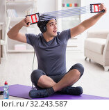 Man doing sports with resistance band and listening to music. Стоковое фото, фотограф Elnur / Фотобанк Лори