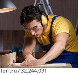 Купить «The worker working in repair workshop in woodworking concept», фото № 32244091, снято 11 августа 2017 г. (c) Elnur / Фотобанк Лори