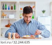 Купить «Young husband eating tasteless food at home for lunch», фото № 32244635, снято 24 апреля 2017 г. (c) Elnur / Фотобанк Лори