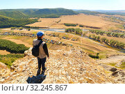 Купить «Man Tourist with a backpack is on top of the High Rock Mountain below, the Zilyim River flows against the background of the Ural Mountains. Autumn sunny day.», фото № 32245867, снято 30 августа 2016 г. (c) Акиньшин Владимир / Фотобанк Лори