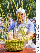 Russia, Samara, 2016: The wise man is weaving a basket from a vine at a flower festival. Samara. Редакционное фото, фотограф Акиньшин Владимир / Фотобанк Лори