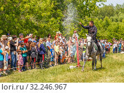 """Купить «Russia, Samara, June 2016: A dashing Cossack knocks down the sword of a bottle of water on a horse during the demonstration performances at the """"Journey to the Past"""" festival.», фото № 32246967, снято 18 июня 2016 г. (c) Акиньшин Владимир / Фотобанк Лори"""