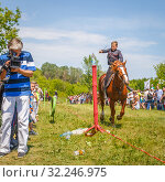 """Купить «Russia, Samara, June 2016: A dashing Cossack knocks down the sword of a bottle of water on a horse during the demonstration performances at the """"Journey to the Past"""" festival.», фото № 32246975, снято 18 июня 2016 г. (c) Акиньшин Владимир / Фотобанк Лори"""