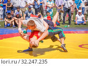 Купить «Russia, Samara, May 28, 2016: fight kuresh at Sabantuy in the city park. This struggle on the canvas, thrown at the enemy's belt, an important element of the national holiday among peoples.», фото № 32247235, снято 28 мая 2016 г. (c) Акиньшин Владимир / Фотобанк Лори